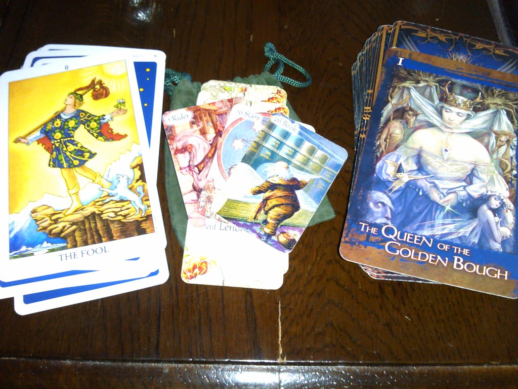 From left to right: a tarot deck (Radiant Rider-Waite), a Lenormand deck (Kendra's Vintage Petit Lenormand), and an oracle deck (Heart of the Faerie Oracle).